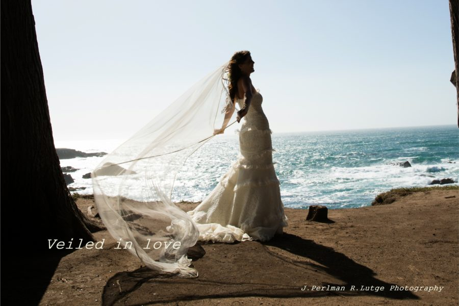 Kristina sweeps back her veil to the breeze near the bluffs after her Elope Mendocino wedding.